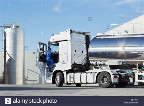 truck driver climbing into stainless steel milk tanker stock photo royalty free image 68144660
