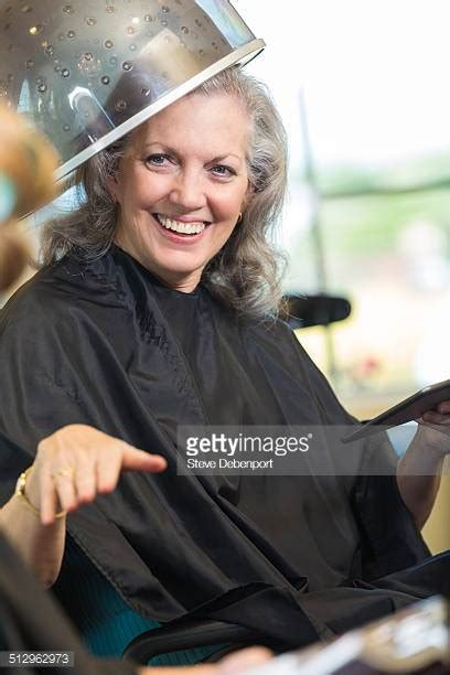 woman sitting under hair dryer hair salon old women stock photos and pictures getty images