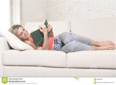 lying on couch young beautiful caucasian woman reading book studying