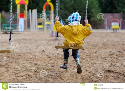 rain swing small girl in yellow rain coat on swing stock image
