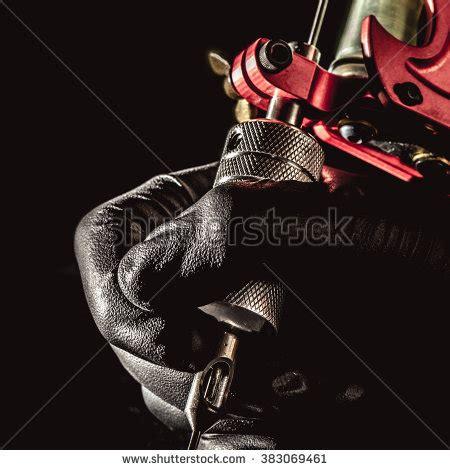 tattoo machine up close closeup of a gloved hand holding a tattoo machine on black