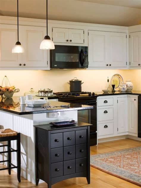 white kitchen with black appliances white cabinets and backsplash black counters and