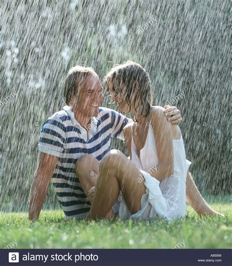 the bench com romantic couple sitting on lawn in rain stock photo