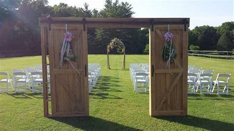 Barn door wedding aisle entrance with rustic ceremony arch
