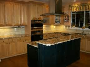 medium oak cabinets with a black island search