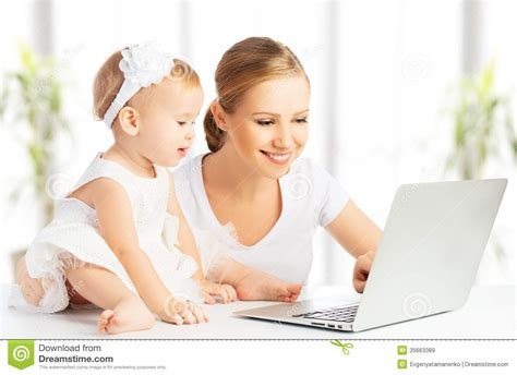 and baby with computer working from home stock image