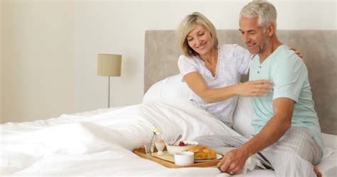 husband and wife bedroom romance couple chatting and having breakfast in bed at home in