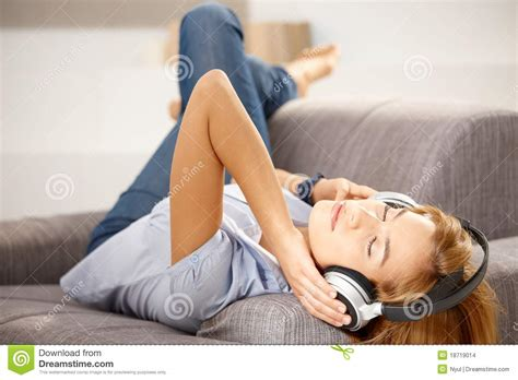 laying on couch attractive girl enjoying music laying on sofa stock images