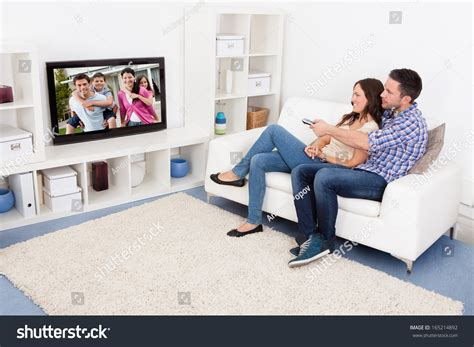 you sitting on the couch watching tv happy young couple livingroom sitting on stock photo