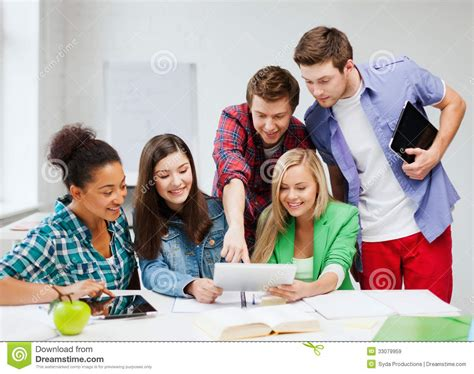 Royalty Free School Children Stock by Students Looking At Tablet Pc At School Royalty Free Stock