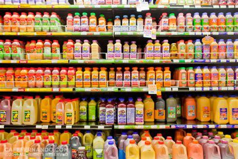 Shelf Of Orange Juice by Fresh Juice Versus Bottled Juice With Greens