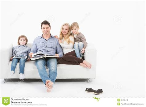 couch family happy family on the couch reading a book stock photo