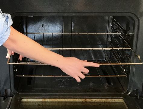 woman cleans  oven racks    clean