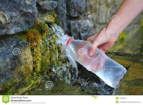 what is a spring source of spring water bottle filling holding hand stock
