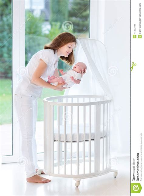 when to put baby in toddler bed mother putting her newborn baby to sleep in crib stock