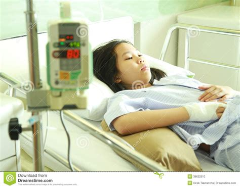woman in hospital bed woman patient in hospital bed with iv machine stock photo