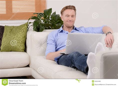 a man and a couch men relaxing with laptop young cheerful men using laptop