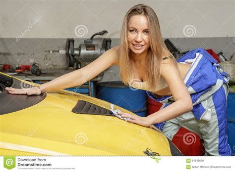 pretty girl mechanic polishes  car hood stock photo