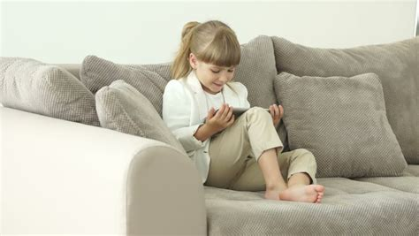 little girls sofa little girl sitting on the couch with a tablet and talking