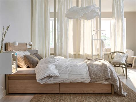 a bed in oak with bed textiles in white beige and light brown