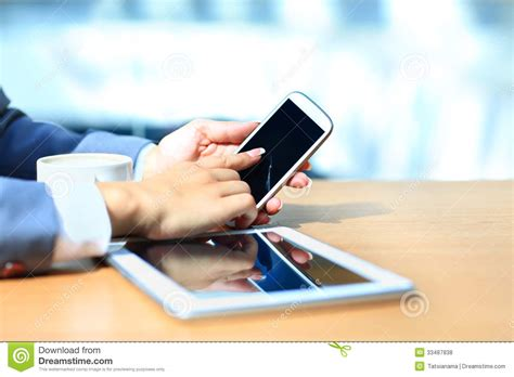 business lady uses a tablet and phone to work the girl in the