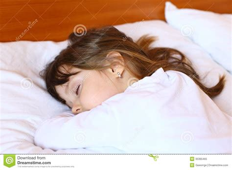 how to get her in bed little girl sleeping peacefully in her bed royalty free