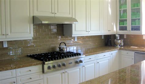Chagne Glass Subway Tile Backsplash With White Cabinets