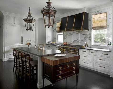 range hood sarl in the french a black kitchen with brass straps stands a marble cooktop backsplash and a