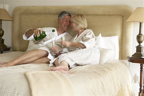 bedroom sex download middle aged couple enjoying chagne in bedroom stock