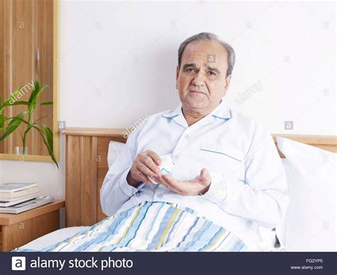 old bed guy old man in sad mood holding pill bottle sitting on bed mr