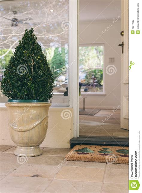 open front door with welcome mat and decorative topiary stock photo image 45319862