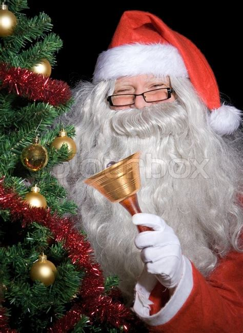 img of santa claus and x mas tree santa claus with handbell beside tree stock photo colourbox