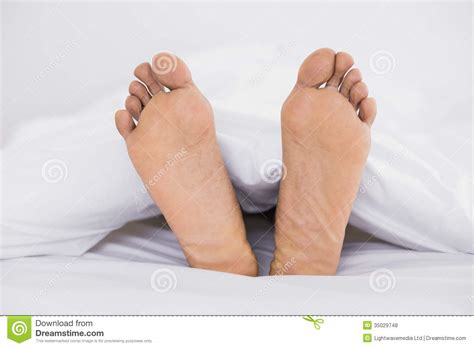 bed feet close up of bare feet in bed royalty free stock photos