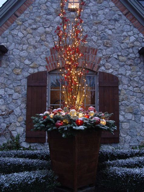 christmas decorating huge stone urns in front of entrance planter with lighted branches outdoor decorating planters