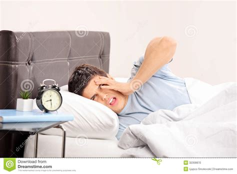 guy in bed guy lying on a bed and gesturing late stock photo image