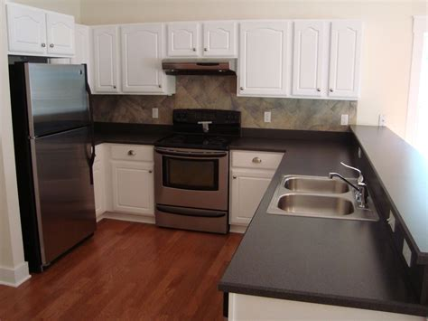 white kitchen cabinets stainless steel appliances love the slightly darker red tone floor with the white