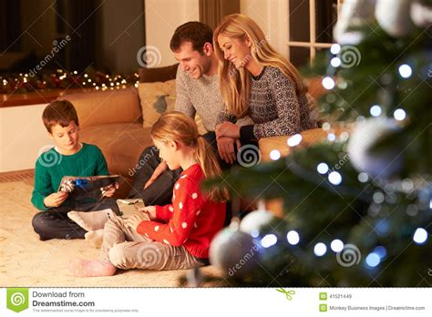 family unwrapping gifts by christmas tree stock image