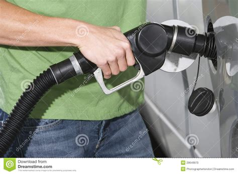 mid section mid section of a man in casuals refueling his car stock