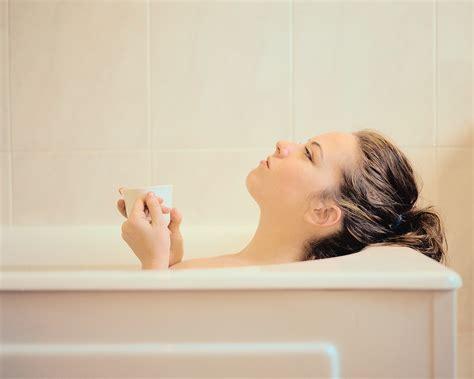 frau in badewanne lying in a bathtub holding a mug successful living