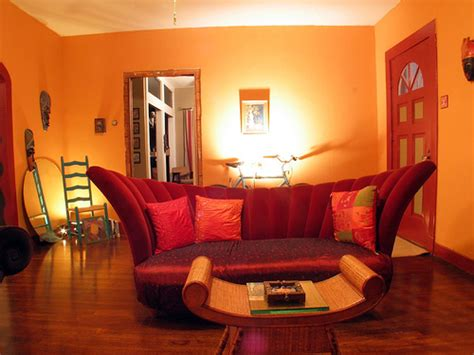red and orange living room the deep red couch and door along with the orange create a