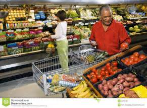 Middle aged african american man and woman in grocery store shopping