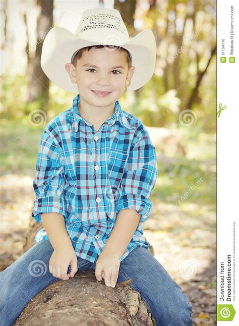 portrait of two year old boy with red curly hair stock boy with cowboy hat on tree trunk stock photo image