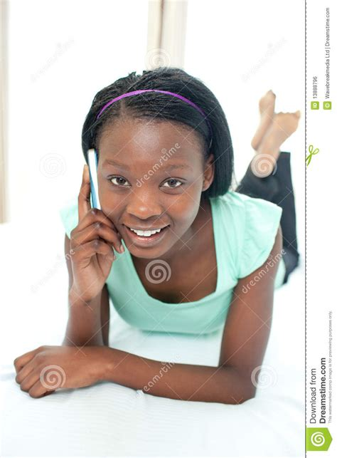 smiling girl using mobile phone in bed royalty free stock smiling teen girl using a mobile phone royalty free stock