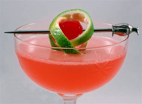 martini twist file pink lady with a twist of lime in a cocktail glass