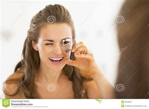 women using the bathroom young woman using eyelash curler in bathroom royalty free stock photography image