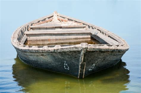 Old fishing boat floating on the water stock photo colourbox