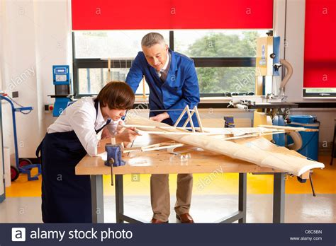 teaching woodworking and student in woodworking class working on model