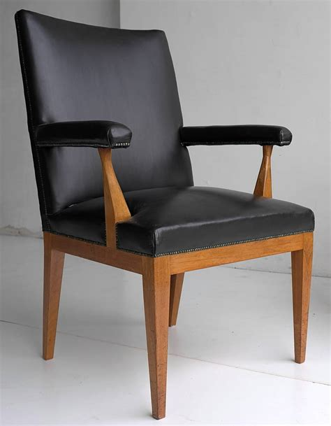 pair of black leather and rosewood office chairs by theo