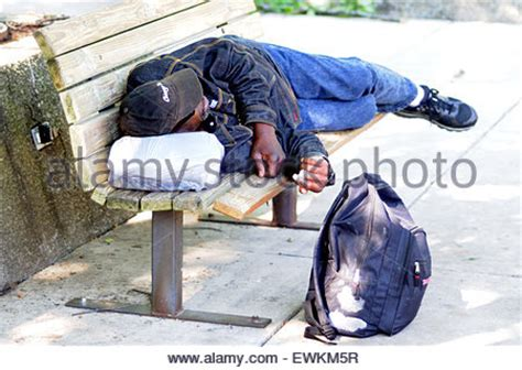 homeless man on bench a homeless man is sleeping on a bench in a park in
