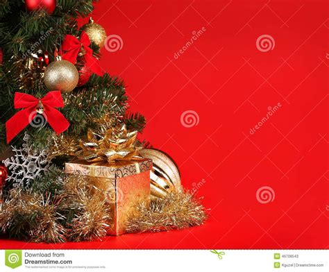 christmas gift box under christmas tree over red